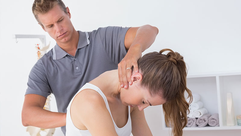 Woman being treated by chiropractor for auto accident injury