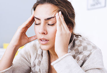 Woman sufferinf from headaches in need of Sports Injury Care