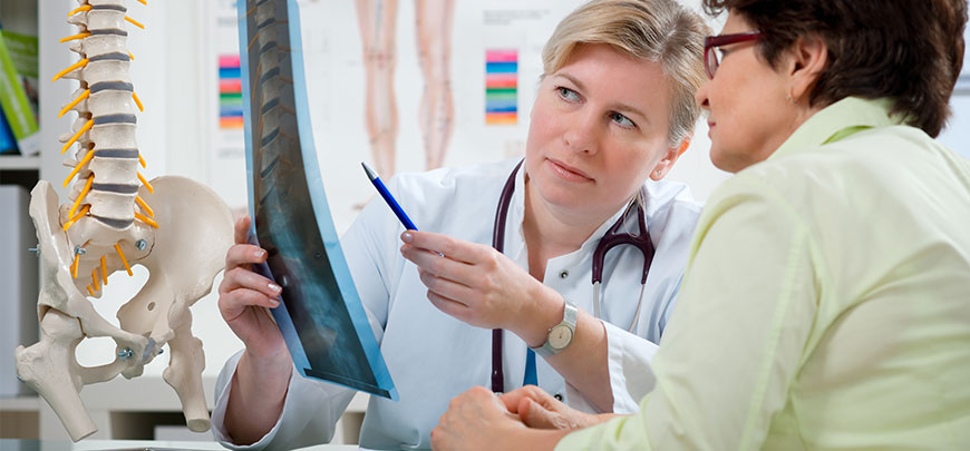 Chiropractor discussing x-ray results with patient