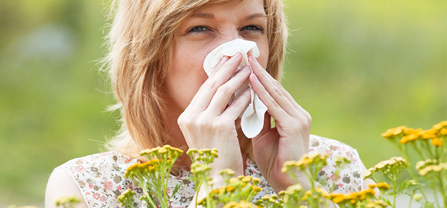Woman suffering with allergies in a field of flowers