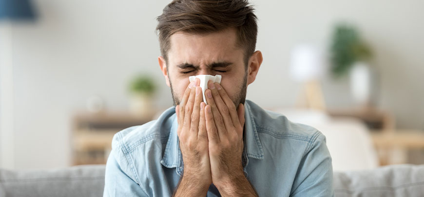 Man suffering at home with severe allergies